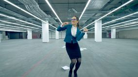 Female worker dances alone in a room, throwing paper. 4K stock video