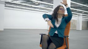 Female worker dances, sitting in an office chair, having fun. 4K stock video