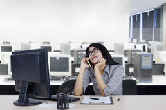 Female worker daydreaming with mobile phone. Portrait of female worker listening her mobile phone while daydreaming in the office Royalty Free Stock Photography
