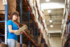 Female Worker In Distribution Warehouse. Looking at clipboard stock photo