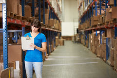 Female Worker In Distribution Warehouse. Looking to clipboard royalty free stock image