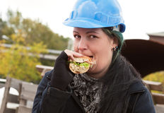 Female worker eating sandwich Royalty Free Stock Photos