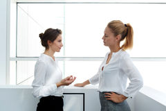Female worker explaining to her dissatisfied boss why she was late for work while standing in office interior, Royalty Free Stock Image