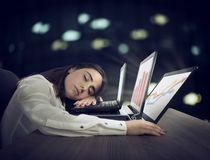 Female worker falls asleep while simultaneously working on three laptops. Businesswoman asleep on top of three laptops royalty free stock images