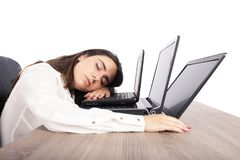 Female worker falls asleep while simultaneously working on three laptops royalty free stock photography
