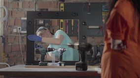 Female worker on the furniture factory testing the drill screwdriver. The woman with tattoos on hand working in the. Modern workshop. The profession of the stock video footage
