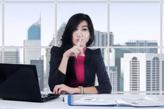 Female worker gesturing silence. Portrait of beautiful businesswoman working in the office and gesturing silence Royalty Free Stock Image