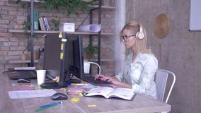 Female worker in glasses and headphones working on personal computer in a modern creative office stock video footage