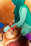 Female worker grinding Argan nuts Stock Images