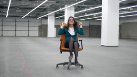 Female worker having fun, riding an office chair. 4K stock video footage