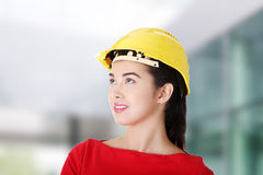 Female worker in helmet looking up. Royalty Free Stock Photo