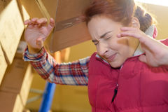 Female worker hitting head by accident into shelf Stock Image