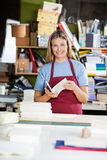 Female Worker Holding Paper While Making Notepad Stock Image