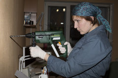 Female worker keeps electrical drill Stock Photography
