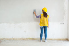 Female Worker, Labor Plastering White Concrete Wall at Home, Hou. Se Construction Site as Interior Civil Renovation Work concept Royalty Free Stock Photo