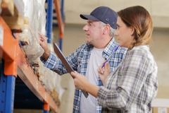 Female worker and manager holding clipboard in warehouse Stock Photos