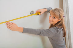 Female worker measuring white wall Royalty Free Stock Photos