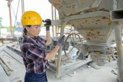 Female worker mixing ingredients in concrete mixer Royalty Free Stock Photo