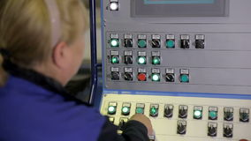 Female worker operating industrial control panel, display at a modern industrial equipment. HD stock video footage