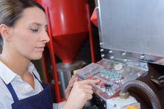 Female worker operating machine in factory. Female worker operating a machine in a factory Royalty Free Stock Photo