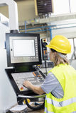 Female worker operating machinery at control panel in factory Royalty Free Stock Image
