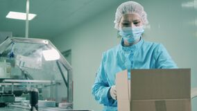 Female worker is packing up pharmacology products