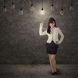 Female worker pointing at bright lamp Royalty Free Stock Images
