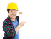 Female Worker Points at Sign Royalty Free Stock Image