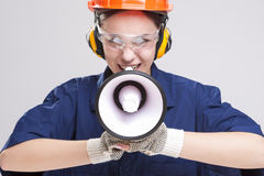 Female Worker Posing with Megaphone and Wearing Hardhat for Protection. Stock Photography