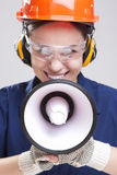 Female Worker Posing with Megaphone and Wearing Hardhat for Protection. Vertical Image Composition Royalty Free Stock Image