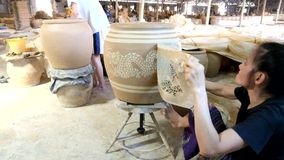 Female worker prints Dragon pattern on clayed jar stock video footage