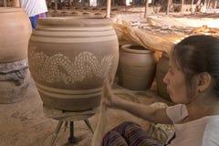 Female worker prints Dragon pattern on clayed jar. Dec 18, 2017 - Ratchaburi, Thailand: female worker prints Dragon pattern on clayed jar, one of making famous stock image