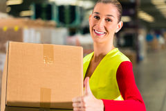 Worker holds package in warehouse of forwarding. Female worker with protective vest holds package, standing at warehouse of freight forwarding company stock image