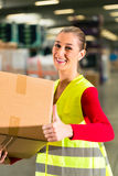Worker holds package in warehouse of forwarding. Female worker with protective vest holds package, standing at warehouse of freight forwarding company stock images