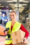 Worker holds package in warehouse of forwarding. Female worker with protective vest and scanner, holds package, standing at warehouse of freight forwarding stock photo