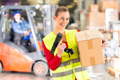Worker holds package in warehouse of forwarding. Female worker with protective vest and scanner, holds package, standing at warehouse of freight forwarding stock images