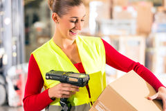 Worker scans package in warehouse of forwarding. Female worker with protective vest and scanner, scans bar-code of package, standing at warehouse of freight stock photos