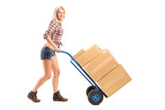 Female worker pushing a handtruck Stock Photos