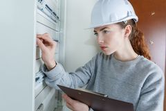 Female worker pushing lever in fuse box. Fuse royalty free stock photos