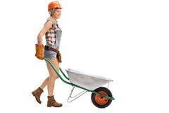Female worker pushing a wheelbarrow Stock Photography