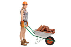 Female worker pushing a wheelbarrow Stock Images