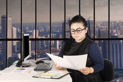 Female worker reading paperworks Royalty Free Stock Image