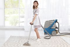 Female worker removing dirt from carpet with professional vacuum cleaner, indoors. Female worker removing dirt from carpet with professional vacuum cleaner stock photography