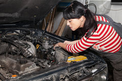 Female worker repairing a car. Woman thinks how to repair a car Stock Images