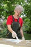 Female worker restoring old wooden door Royalty Free Stock Photography