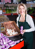 Female worker selling garlic. Mature female worker selling stalks of garlic at market Royalty Free Stock Photos