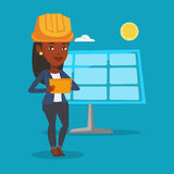 Female worker of solar power plant. Engineer working on digital tablet at solar power plant. African-american worker of solar power plant. Engineer in hard hat Stock Images