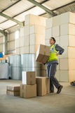 Female worker suffering from back pain while holding heavy box. In factory Royalty Free Stock Image