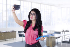 Female worker taking selfie in office Royalty Free Stock Image