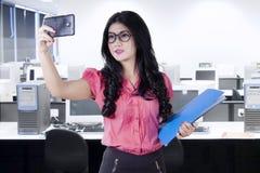 Female worker taking selfie in office Stock Photo
